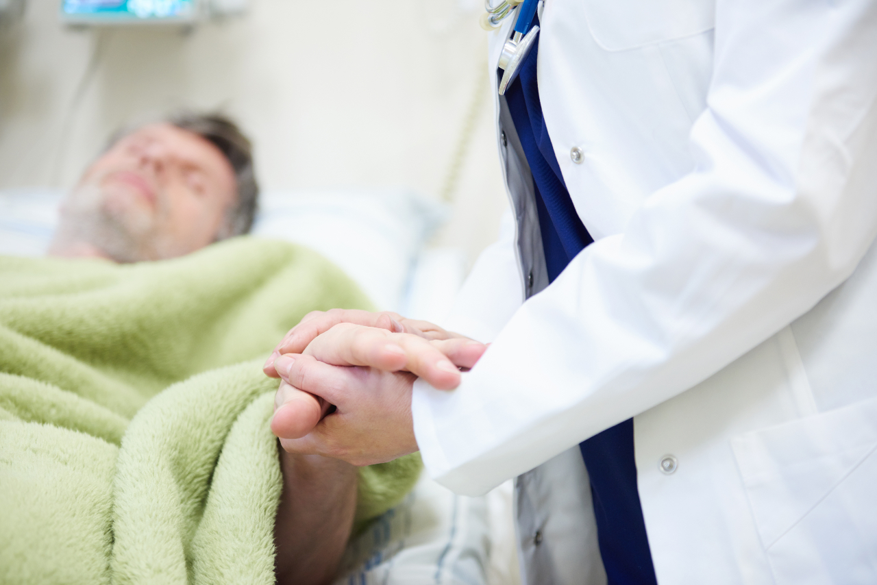 Medical doctor holding hospital patients hand
