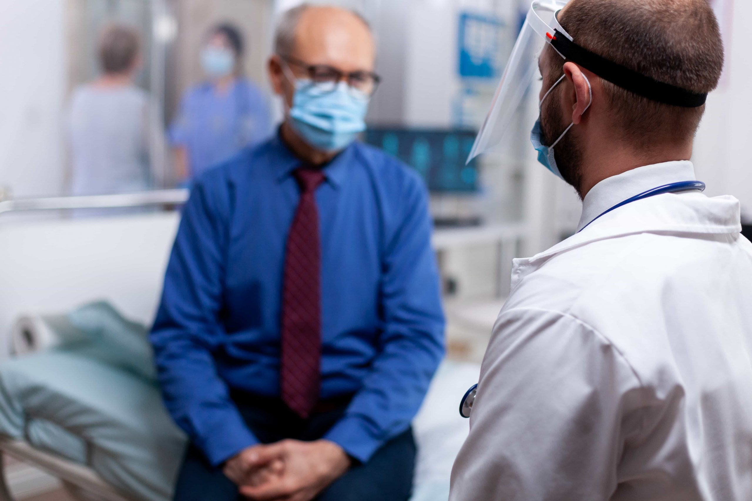doctor in visor talking to patient with mask